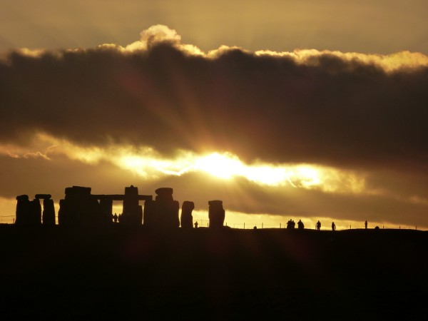 Your Stnoehenge guide - the low winter sun breaks through clouds above Stonehenge