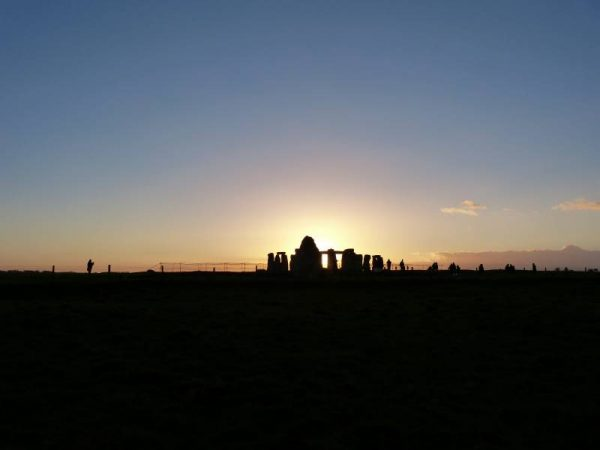 Avebury and Stonehenge guided tours - the sun sinks behind Stonehenge in midwinter