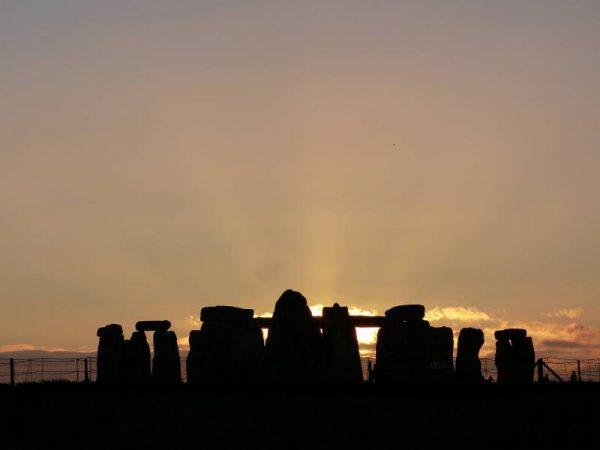 Avebury and Stonehenge guided tours - the midwinter sun sets behind Stonhenge, Wiltshire, UK
