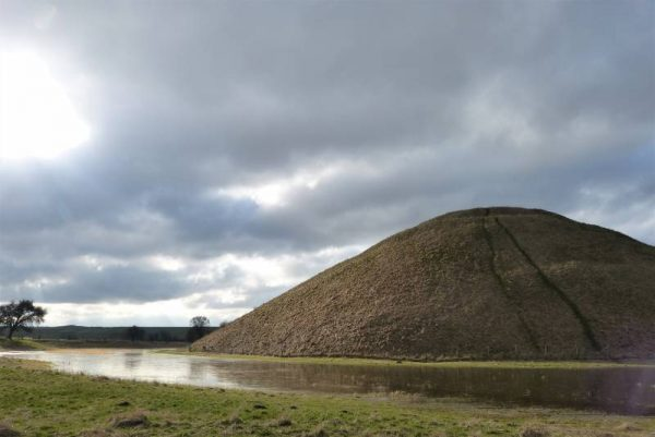 Avebury half day tour: Water and winter skies surround Silbury Hill, Wiltshire, UK