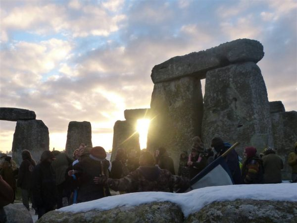 The sun rises between Stonehenge stones