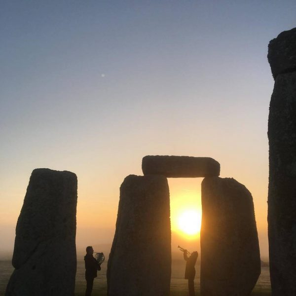 Horn and trumpet players at Stonehenge dawn
